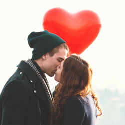 Couple Kissing and holding heart shaped baloon