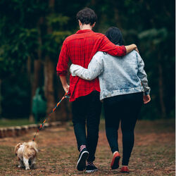 Couple walking in park with dog Photo by Helena Lopes Pexels