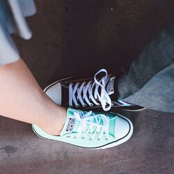 Woman and mans feet wearing converse shoes Photo by Alysa Bajenaru Unsplash