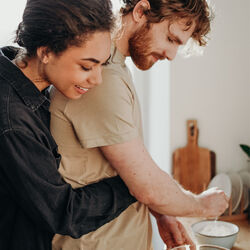 Photo of woman hugging her man whilst cooking Photo by cottonbro from Pexels