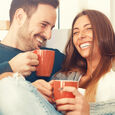Couple sitting drinking from mugs and laughing Photo Thinkstock